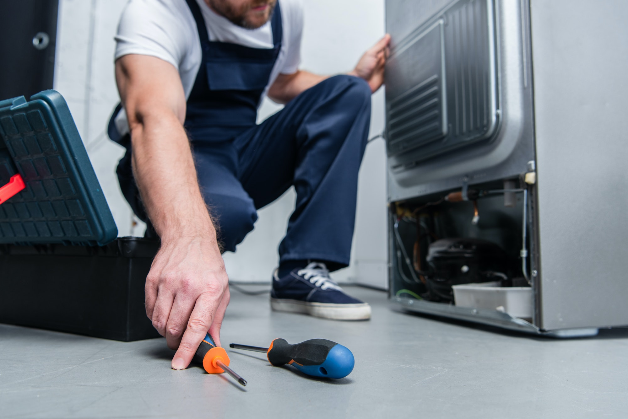 cropped shot of repairman in working overall taking screwdriver from floor near broken refrigerator