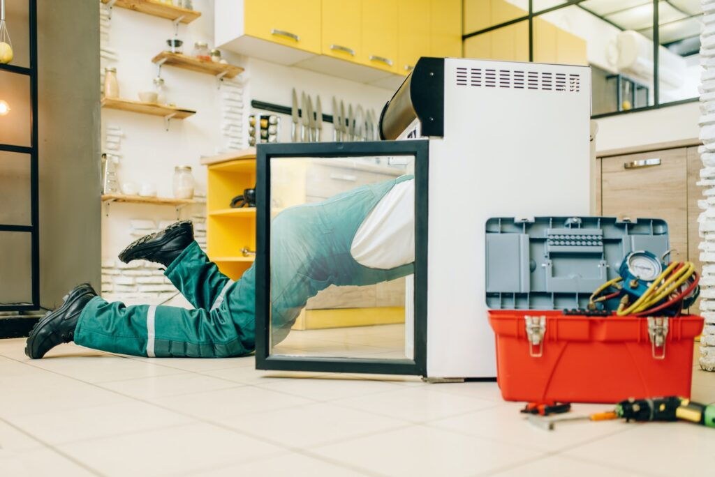 Worker in uniform climbed inside the refrigerator